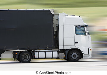 transportation truck - a truck driving on the highway in a...