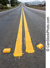 Road with double yellow lines and reflectors - Close up of...