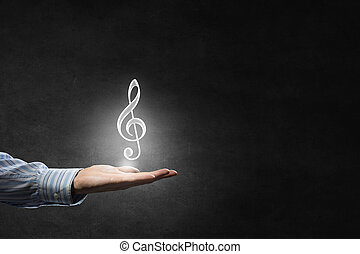 Music icon in hand - Hand of man hold music note icon in...