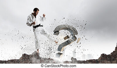 No more doubts - Young determined karate man breaking with...