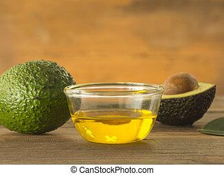 avocado - glass bowl of avocado essential oil with fresh...