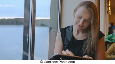 Woman Sitting Near The Window And Using Tablet