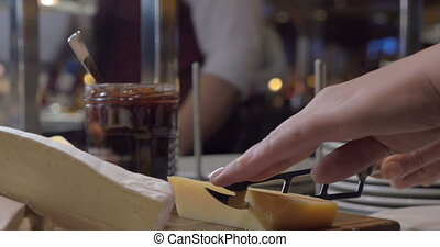 Cutting cheese in the buffet - Close-up shot of female hands...