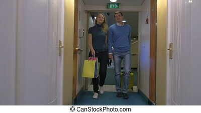 Young couple moving into hotel room - Steadicam shot of...