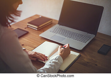 Woman freelancer female hands with pen writing on notebook...