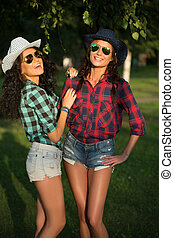Two attractive girls in cowboy hats and sunglasses walking...
