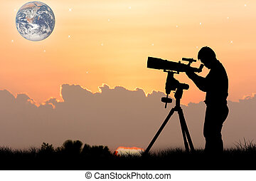 silhouette of young man looking through a telescope at...