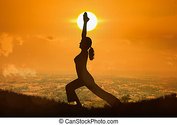 Silhouette young woman practicing yoga at orange sunset...