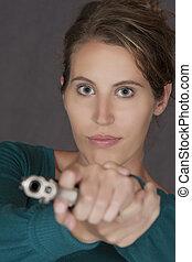 Caucasian woman defending herself using a handgun isolated...
