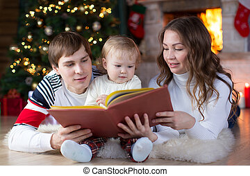 Family reading together on Christmas evening - Family...
