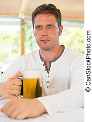 Handsome man with beer in summer cafe.