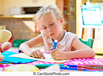 Cute little girl drawing with marker pen