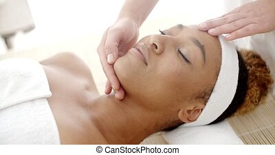 Woman Getting A Face Massage - Young african american woman...