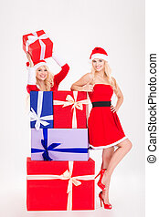 Two smiling woman in santa cloth standing with present boxes...