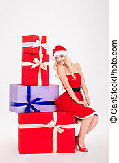 Full length of smiling young woman sitting on gift boxes -...