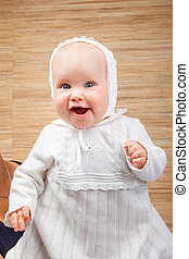 Happy baby in baptismal clothes - Cheerful six month baby...