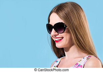 Beautiful smiling young woman with white teeth wearing sunglasses on a blue background