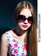 Close-up portrait of a beautiful woman in sunglasses on a...