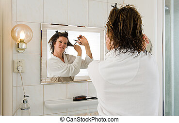 Bad hair day - A woman is looking in the mirror of the...