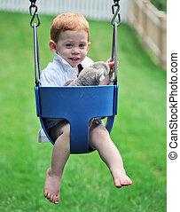 Boy on swing - Cute boy sitting on swing with soft toys