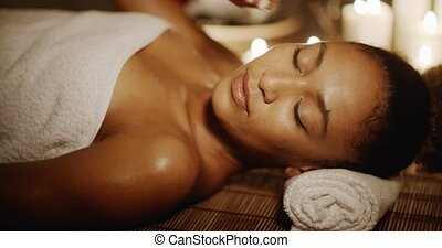 Woman Lying In Spa With Closed Eyes - Young woman lying on...