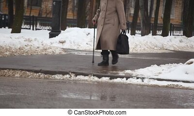 senior woman with walking-stick on winter street