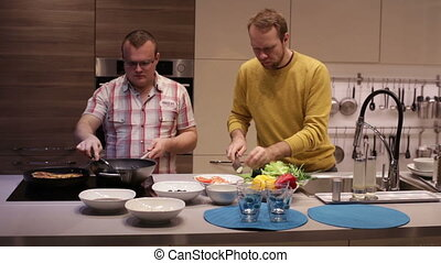 Men preparing dinner in the kitchen and talking