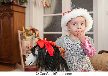 Waiting for Christmas - Little girl with santa hat and...
