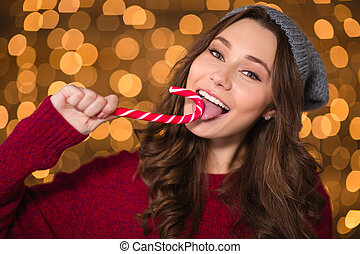 Beautiful happy woman eating candy cane over shining...