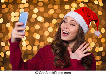 Beautiful happy young woman in santa claus hat using...