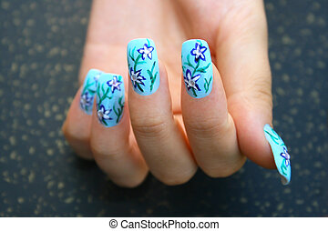 Hand with nail art on spotted background.