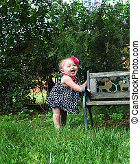 Baby Diva - Baby girl holds onto a wooden bench and...
