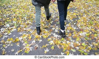 Feet of two persons walking in boots in autumn - Feet of two...