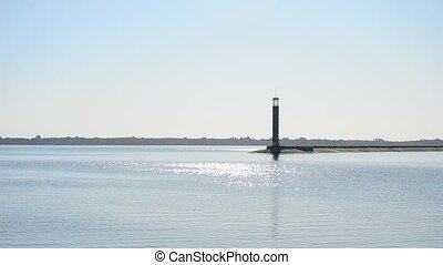 Blue water surface glitters in sunshine with lighthouse -...