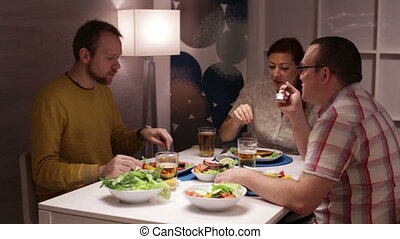 Friends having dinner at the table and talking