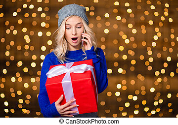 Amazed woman holding present box and talking on the phone