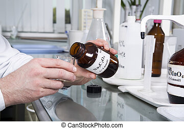 Laboratory bottle with sodium oxalate - Hands of laboratory...