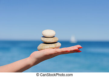 Stones in a hand on a background of the dark blue sky