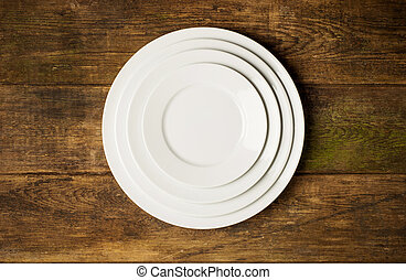 Empty white plate on wooden table top view