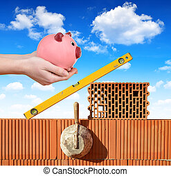 Masonry tools on a brick wall and a hand holding a piggy...