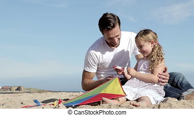 Father and Daughter With a Kite on the Beach - A father is...