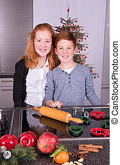 two children in the kitchen preparing christmas bakery