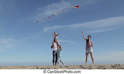 Family flying a kite on the beach - A family of four are...