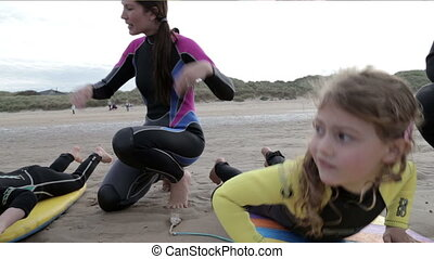 Family of four body boarding in the sea - Two children are...