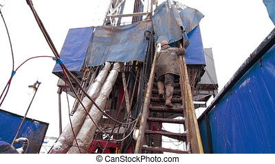 A driller climbing stairs drilling oil rig