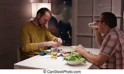 Male friends at table, eating drinking and talking
