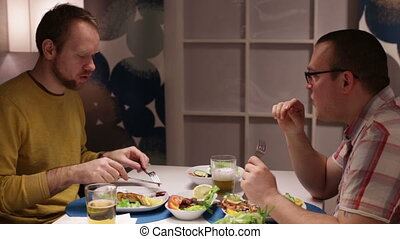 Two friends at table, eating drinking and talking