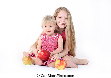 adorable little two sisters 9 year and 1 year old with apple...