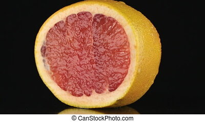 Half of grapefruit, rotating on a black background HD