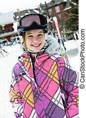 Happy girl in ski helmet at winter resort - Portrait of...